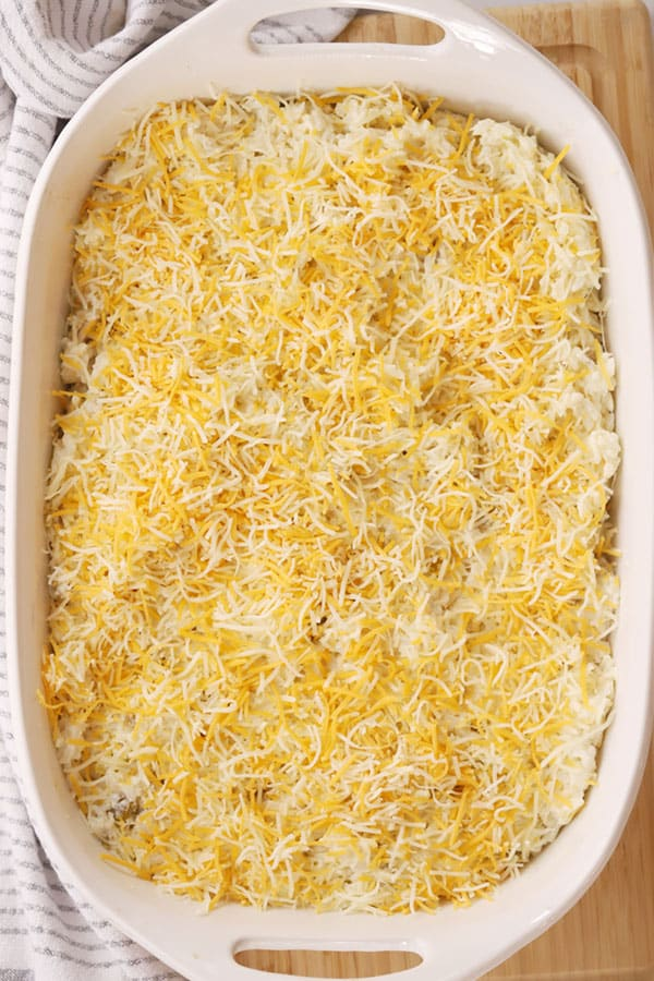Cheesy green chili rice casserole in a baking dish about to go into the oven.
