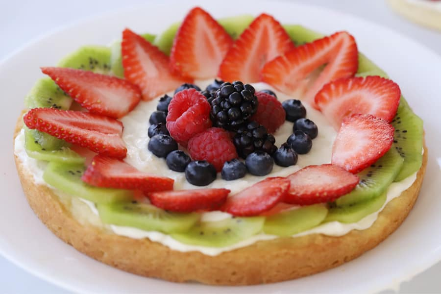 fruit pizza decorated with kiwi, strawberries, blueberries, blackberries and raspberries on a white plate