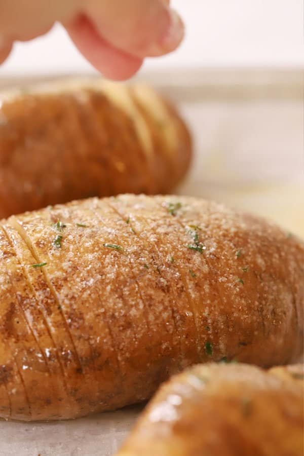 Fingers salting  baked Hasselback Potatoes