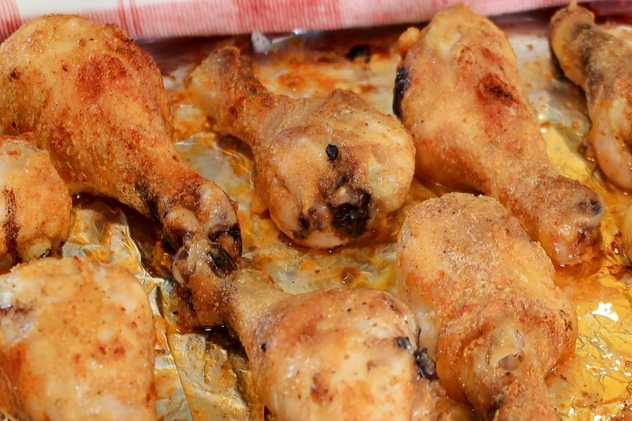 baked chicken drumsticks on a baking pan lined with aluminum foil.