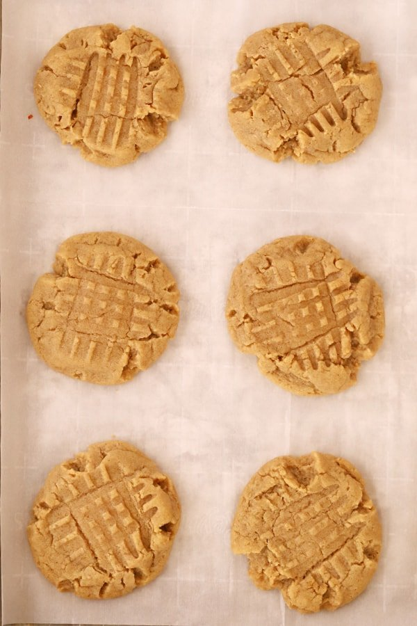 peanut butter cookies with fork marks on a baking tray
