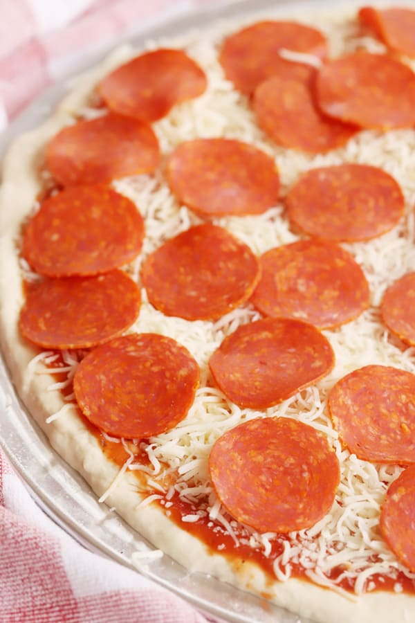 pepperoni pizza, unbaked with a red and white checkered cloth