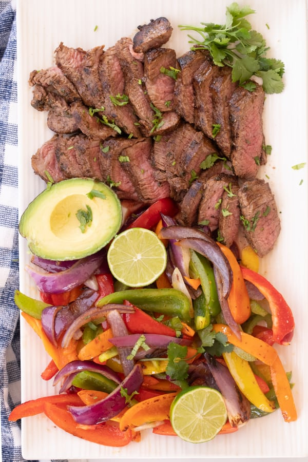 sauteed steak, peppers and onions for steak fajitas displayed on a cutting board