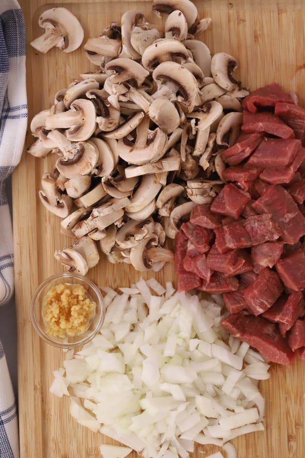 sliced mushrooms, sliced beef, garlic and onions on a cutting board