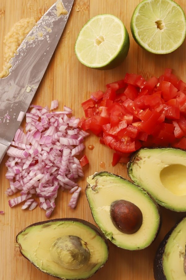 Ingredients to make guacamole being prepped on a cutting board.