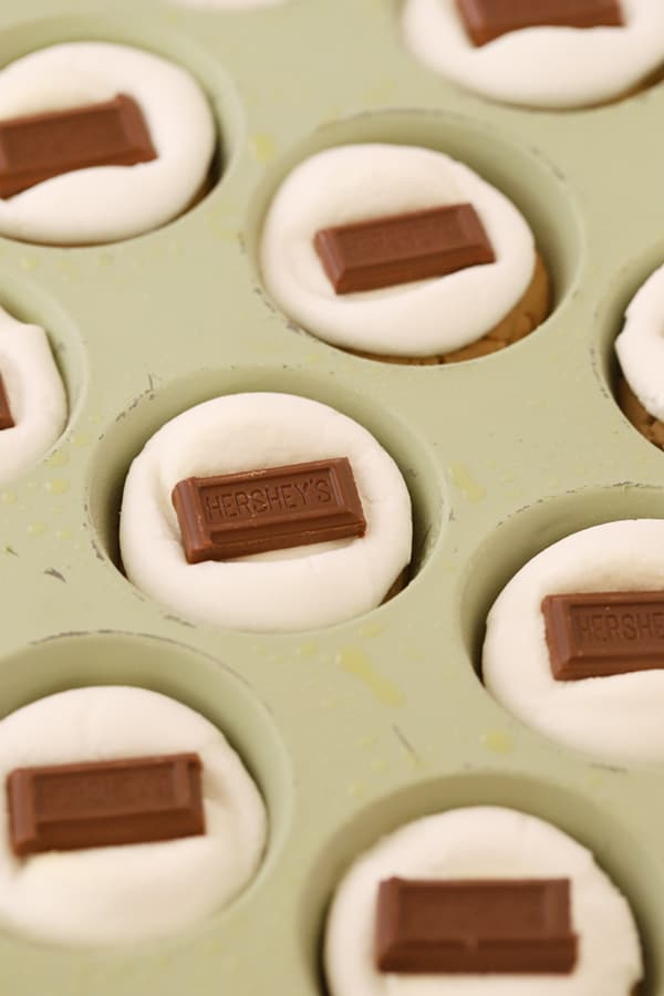 Peanut Butter cookies in a mini muffin tin topped with a large marshmallow and a piece of Hershey's Chocolate.