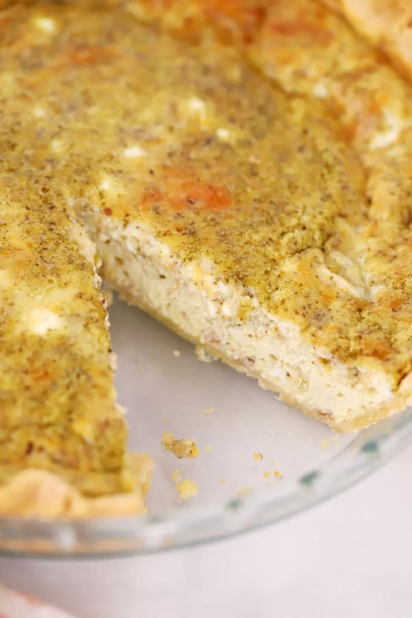 Quiche with a glass pie dish with a slice removed.