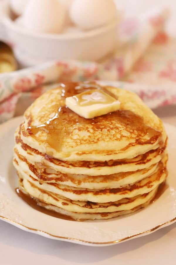 A tall stack of buttermilk pancakes on a white plate, topped with a slab of butter and syrup.