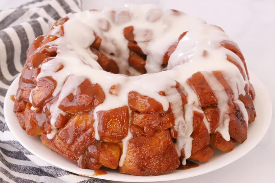 Cinnamon Roll Monkey Bread on a plate covered with icing.