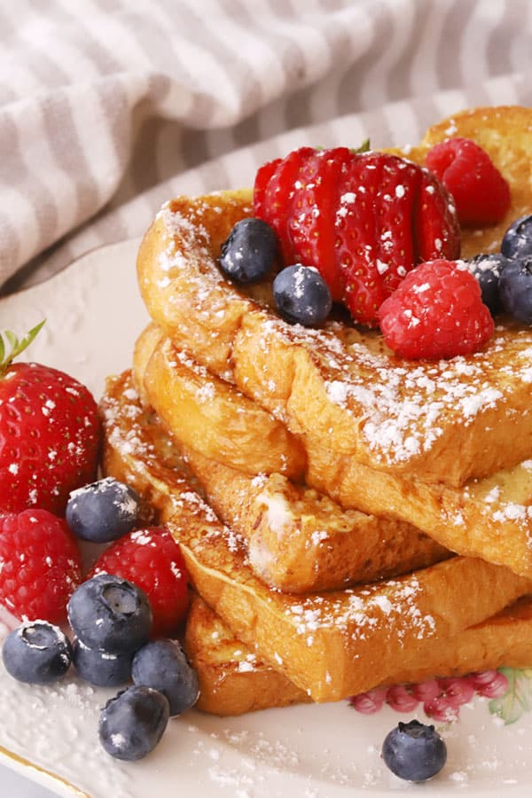 A stack of Classic French Toast on a plate garnished with powdered sugar and fresh berries.