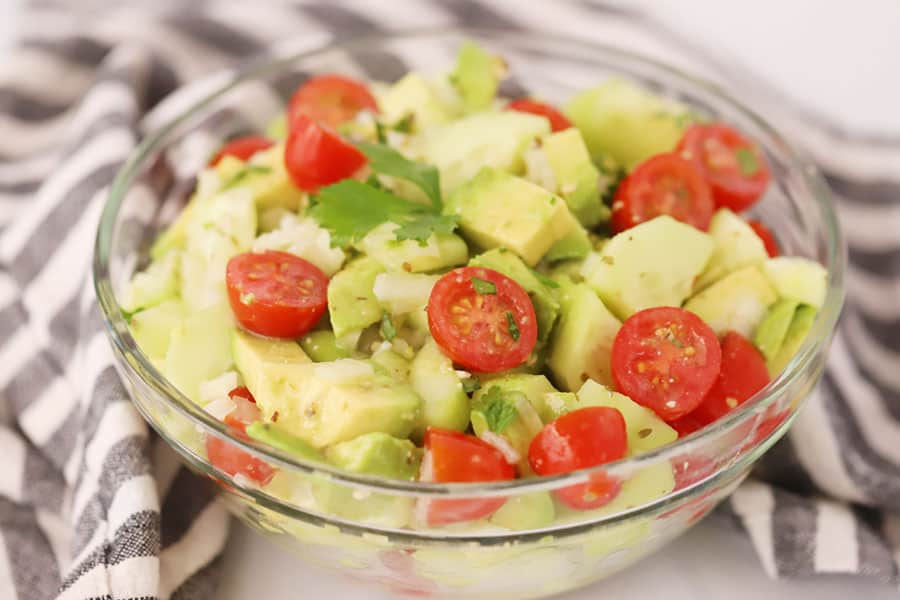 Cucumber tomato avocado salad in a glass bowl.