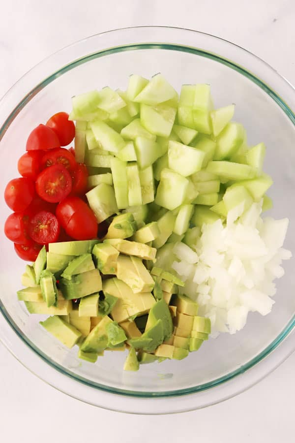 Diced avocados, cucumbers, onions and sliced tomatoes in a glass mixing bowl.