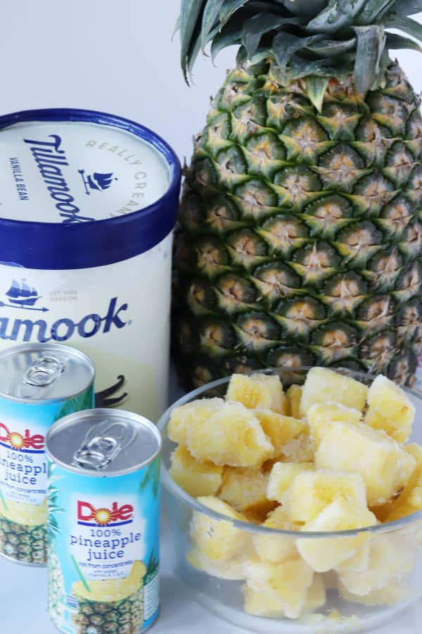 Vanilla ice cream, pineapple juice, frozen pineapple chunks and a whole pineapple out on a table.