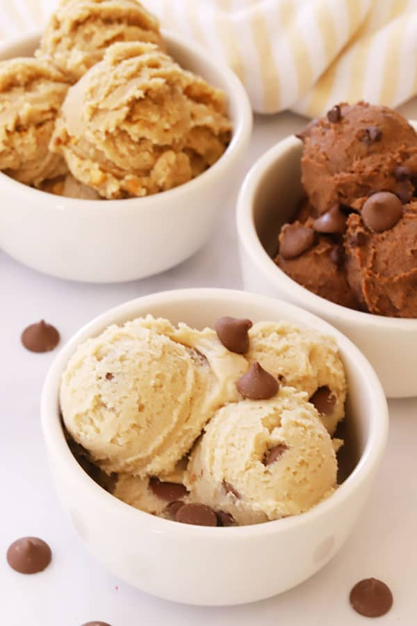 Three small bowls with scoops of edible cookie dough, some garnished with chocolate chips.
