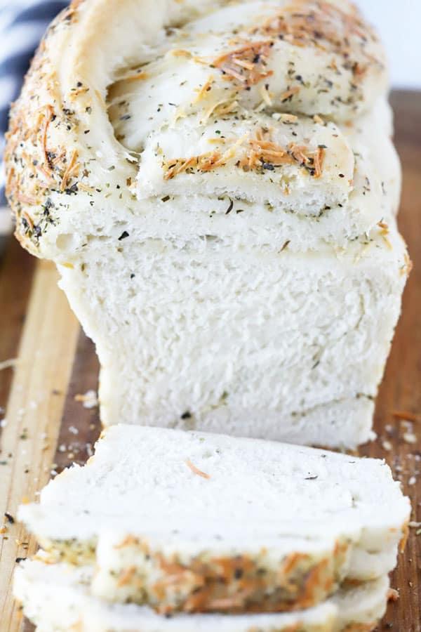 Garlic Herb Twist Bread sliced on a cutting board.