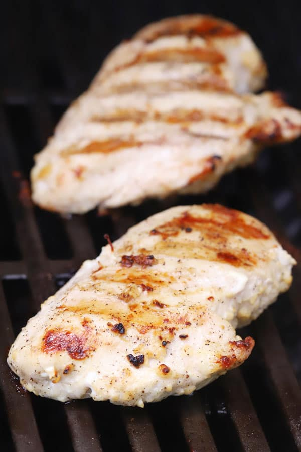 Chicken breasts cooking on a grill.