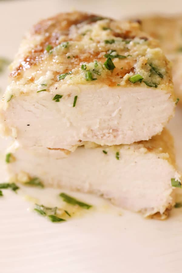 Grilled garlic parmesan chicken breasts cut in half on a plate.