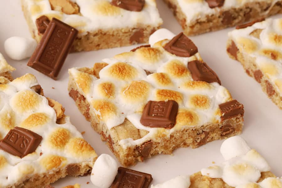 S'mores Cookie Bars cut into squares and garnished with Hershey's chocolate and marshmallows.