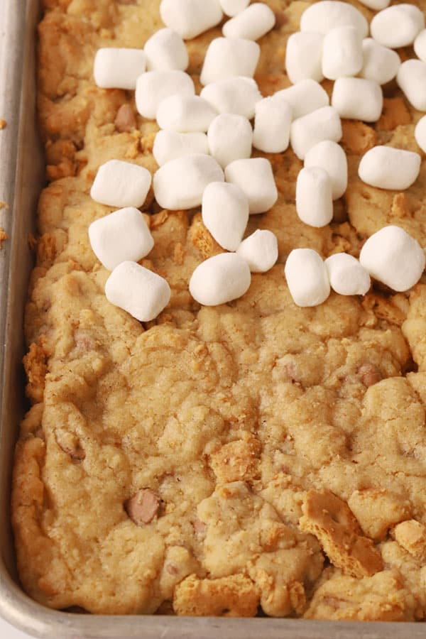 S'mores cookie bar dough baked into a sheet pan, topped with miniature marshmallows.
