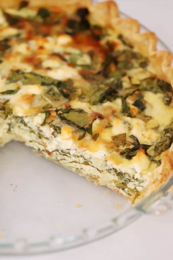 Spinach and Feta Quiche in a pie pan with a slice removed.