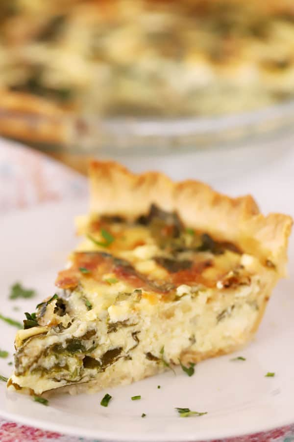Slice of Spinach and Feta Quiche on a white plate.