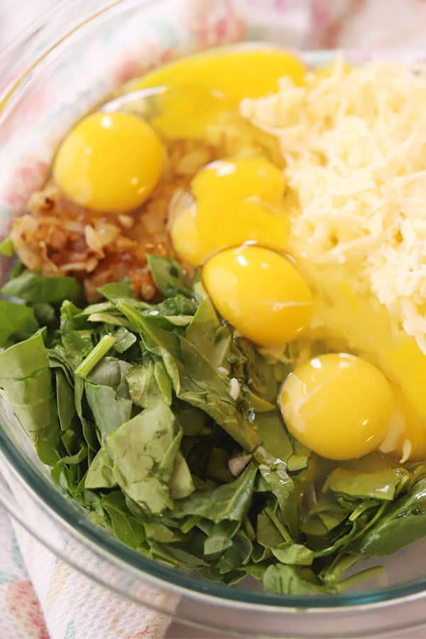 Fresh spinach, cracked eggs and cheese in a clear mixing bowl.