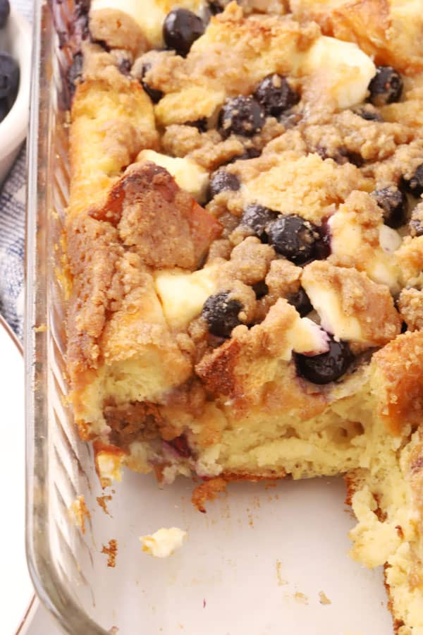 French toast bake in a glass baking dish with blueberries and cream cheese.