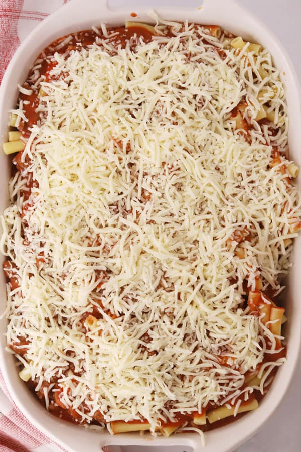 Easy Baked Ziti, covered with red sauce and shredded cheese, being prepped in a baking dish.