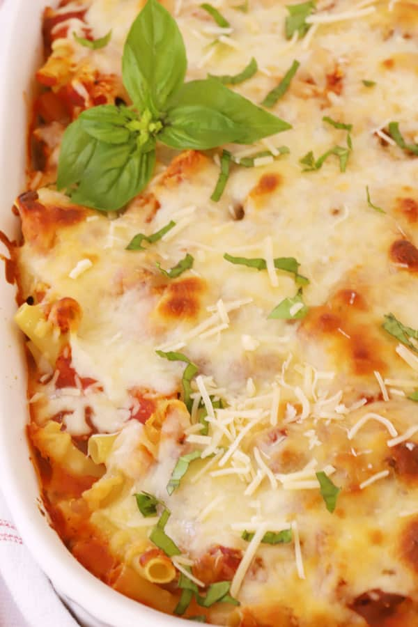 Baked ziti in a casserole dish garnished with fresh basil.
