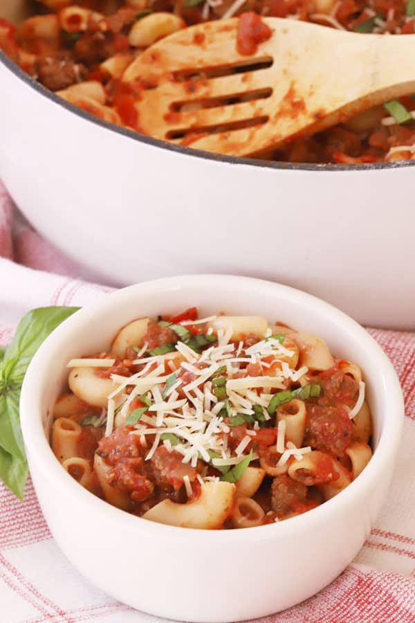 American goulash in a bowl, garnished with shredded cheese and fresh herbs.