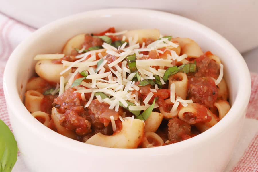 Old-fashioned goulash in a small bowl, topped with shredded cheese and chopped basil.