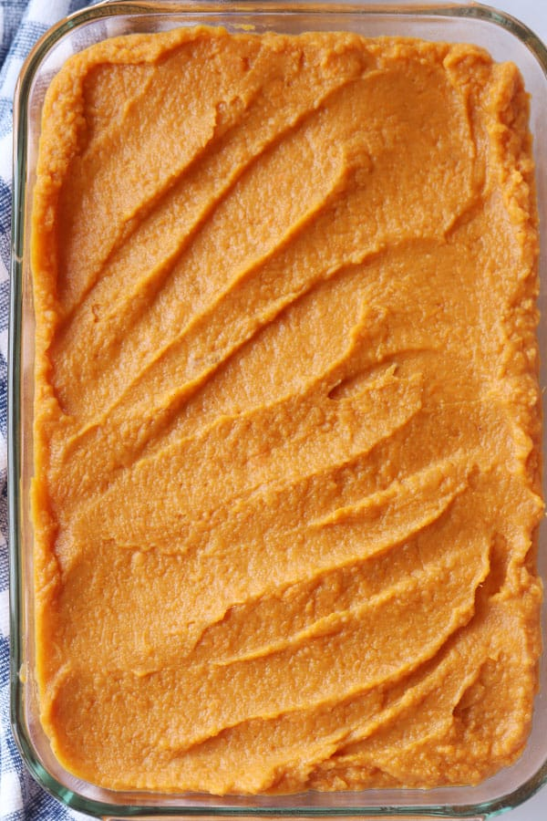 Mashed sweet potato filling spread out evenly in a baking dish.