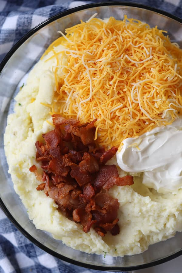 Mashed potatoes, bacon bits, shredded cheddar cheese and sour cream in a glass bowl.