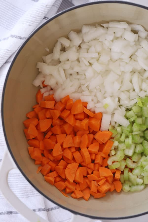 Diced carrots, onions and celery in the bottom of a dutch oven.