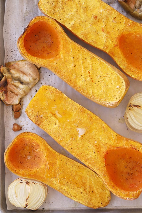 Roasted butternut squash, sliced in half on a baking sheet, ready to be blended into curry squash soup.