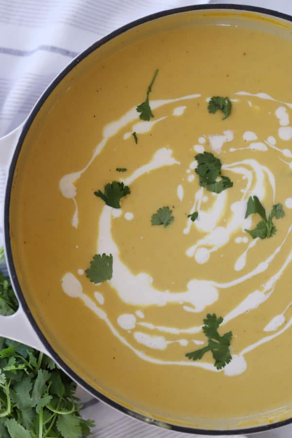 Curry squash soup in a bowl, garnished with sour cream and fresh cilantro.