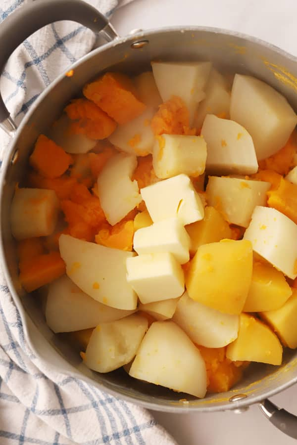 Diced vegetables in a large pot topped with butter.