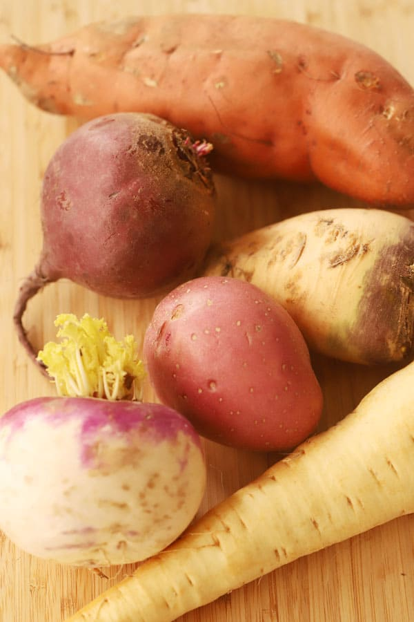 Different root vegetables on a cutting board (sweet potato, beet, rutabaga, parsnip and red potato).
