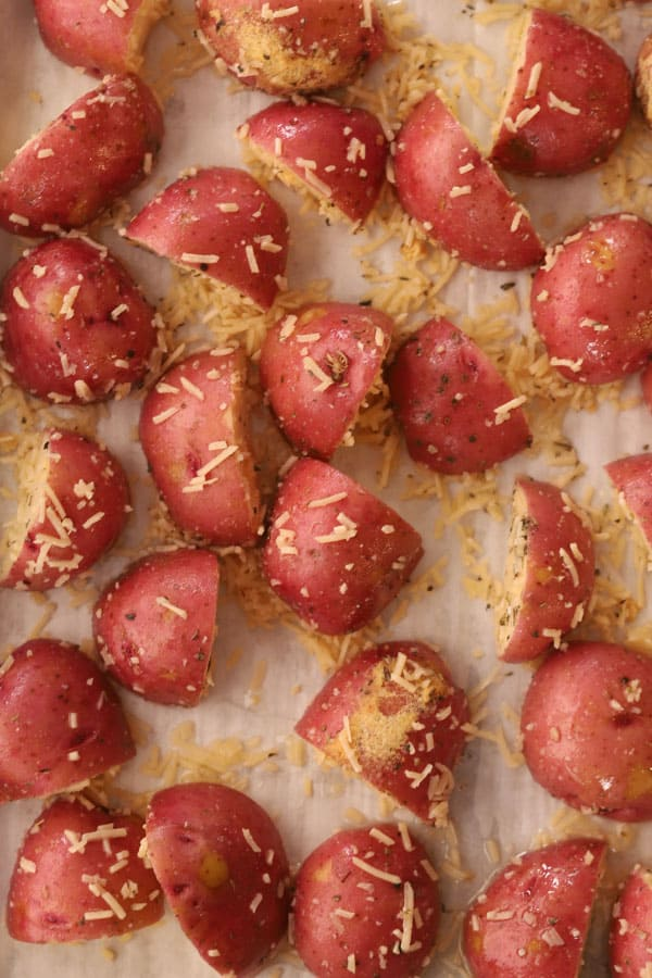 Red potatoes cut into quarters and sprinkled with Parmesan cheese on a baking sheet.