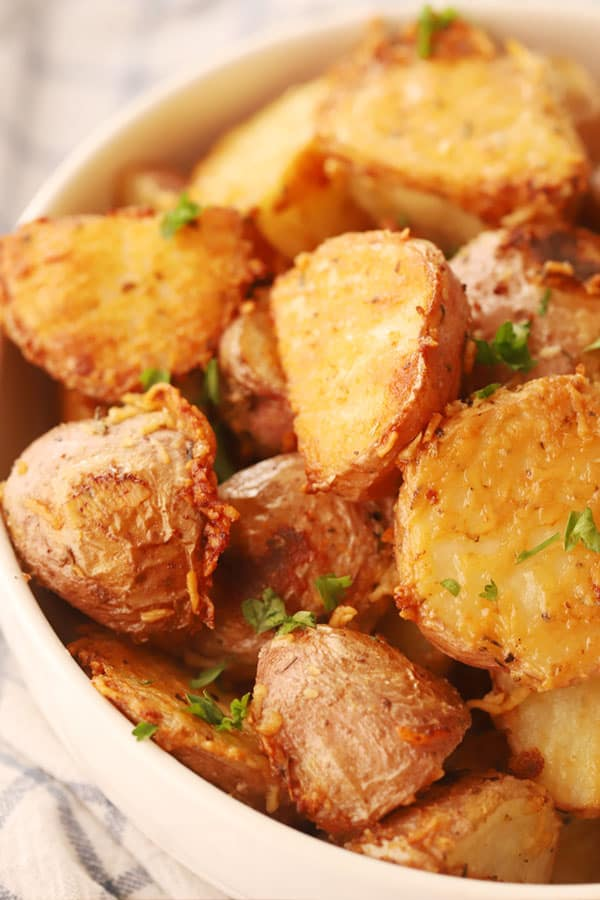 Roasted red potatoes in a bowl garnished with fresh chopped parsley.