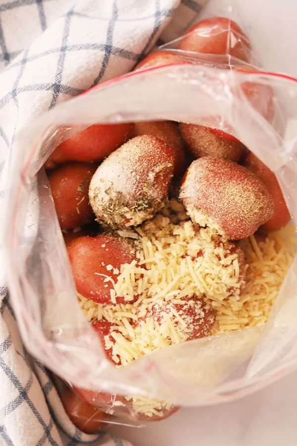 Fingerling potatoes in a ziplock bag with Parmesan cheese and spices.