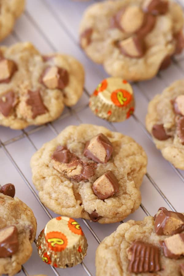 Chocolate Chip cookies topped with Reese's Peanut Butter Cups on a wire rack.