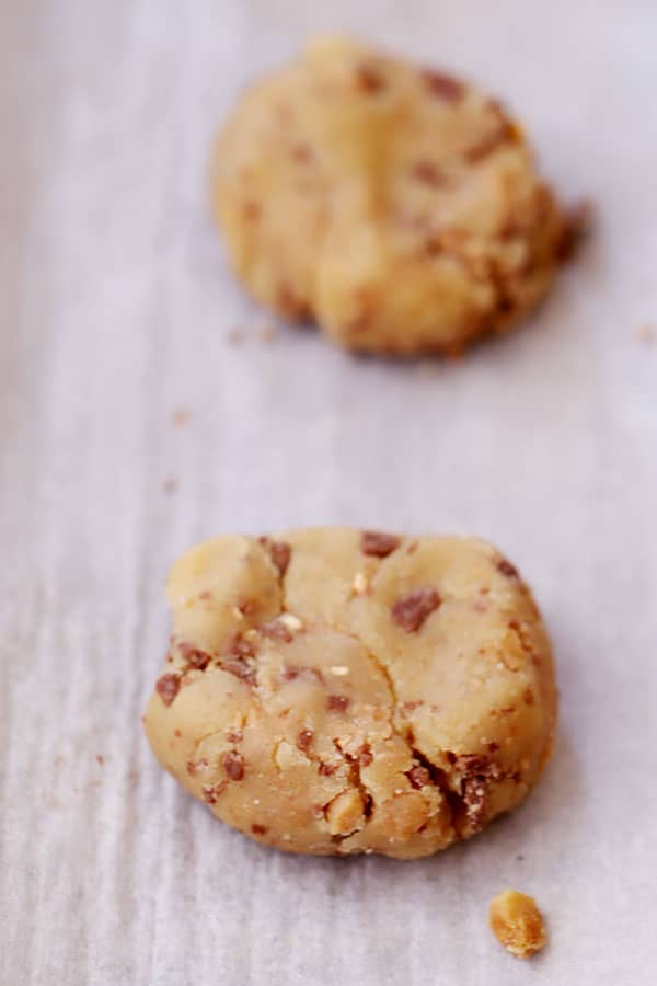 Portioned toffee cookie dough on parchment paper ready to bake.