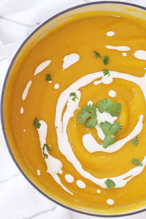 Roasted acorn squash soup in a bowl, garnished with sour cream and fresh cilantro.