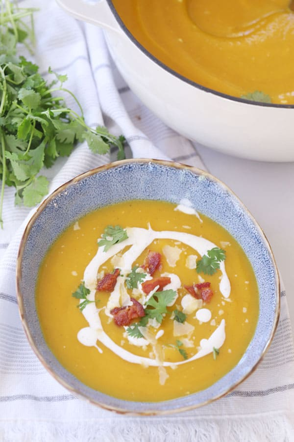 Creamy curry squash soup in a bowl, garnished with bacon, cilantro and coconut cream.