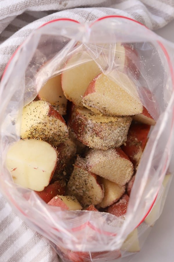 Cut red potatoes covered with seasoning inside a ziplock bag.