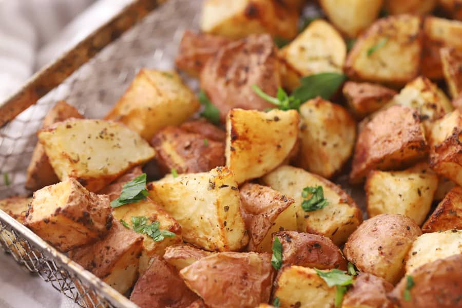 Air fryer red potatoes in an air fryer basket, topped with fresh parsley.