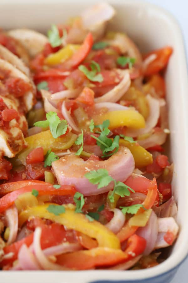 Onions, bell peppers, chicken and diced tomato in a baking dish.