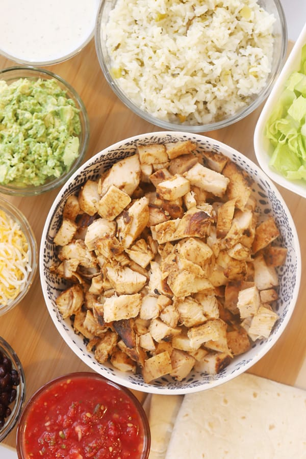 Chipotle chicken in a bowl with side bowls of cheese, guacamole and more.