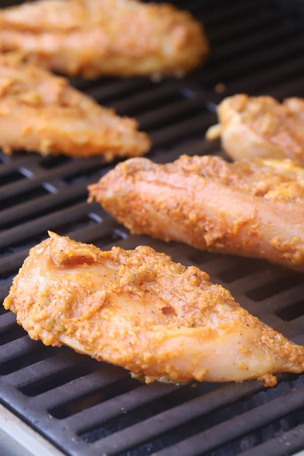Marinated chicken breasts on a grill.